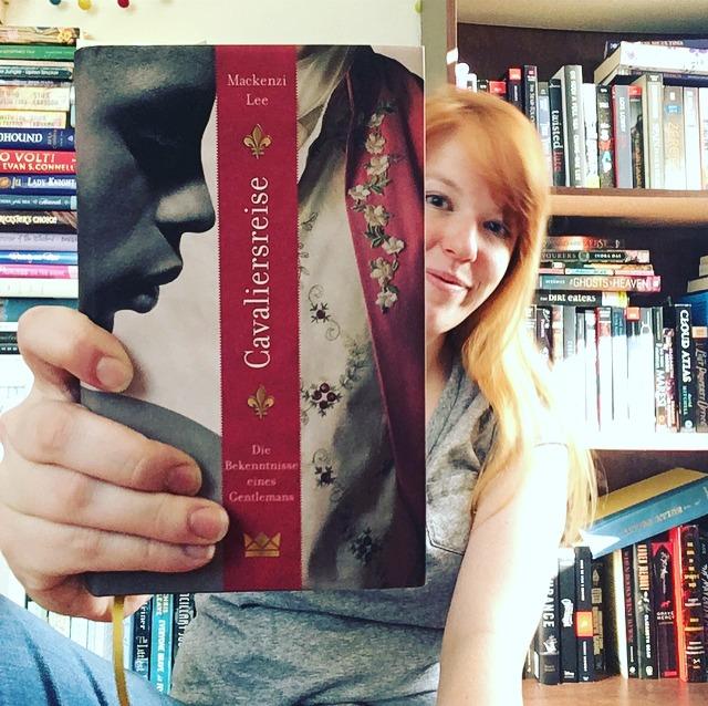 Mackenzi Lee mit ihrem deutschen Buch vor ihrem Bücherregal